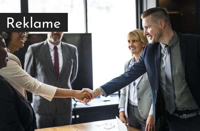 En forretningsmand og en forretningskvinde giver hinanden hånden